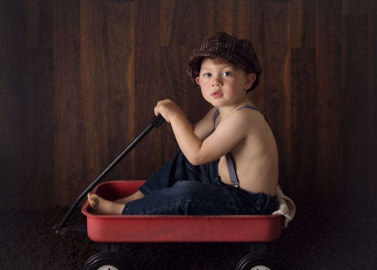 little boy in a red wagon photograph