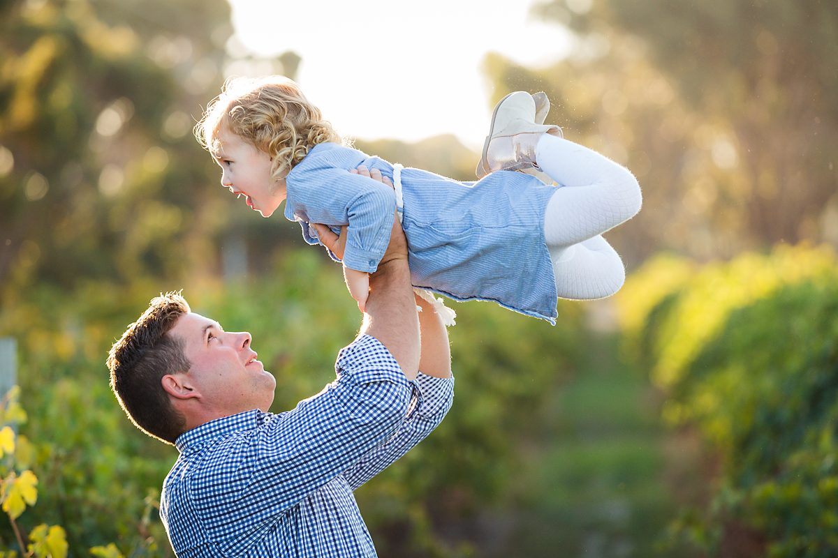 daddy whizzing his little girl around in the vineyards at their family photo shoot by deb elton photography