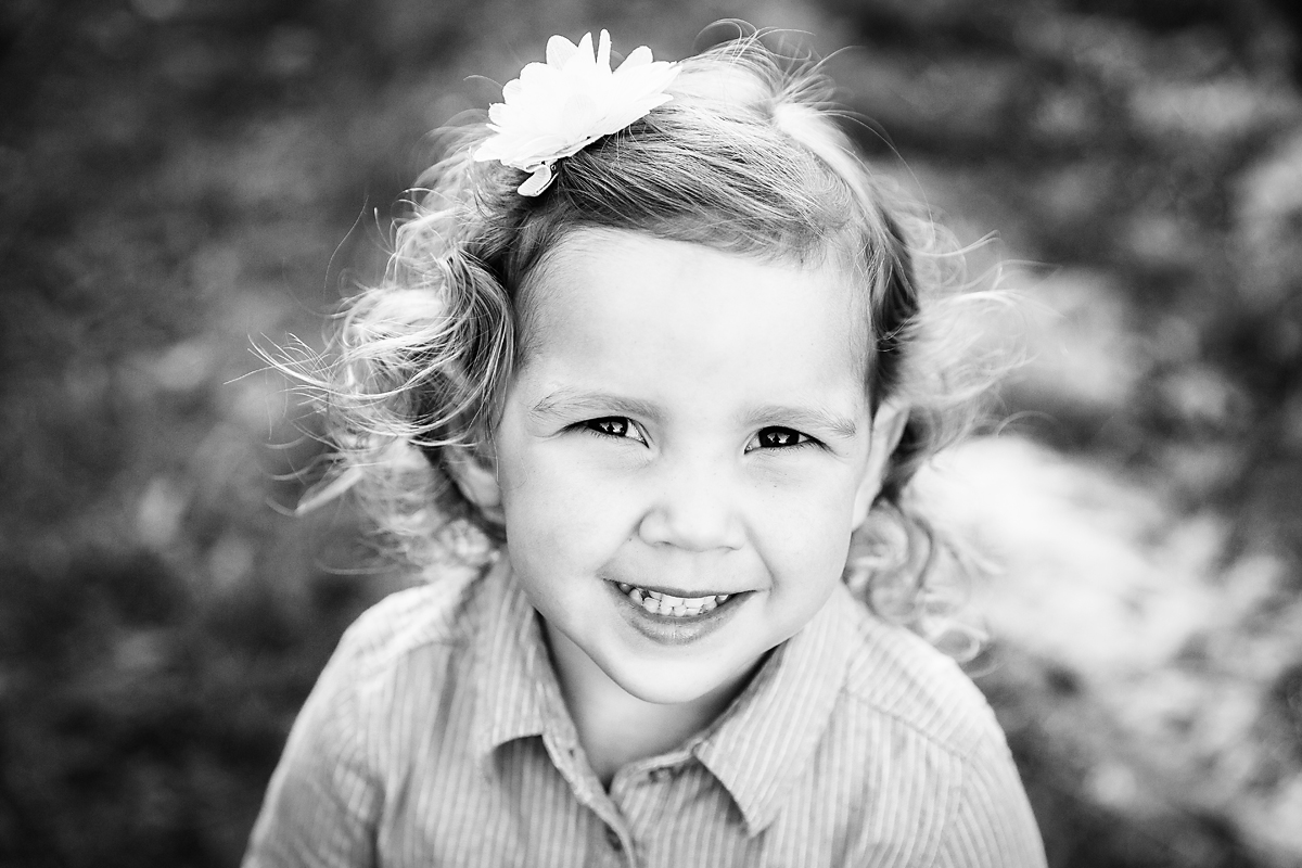 little girl smiling at the camera in the vineyards by deb elton photography