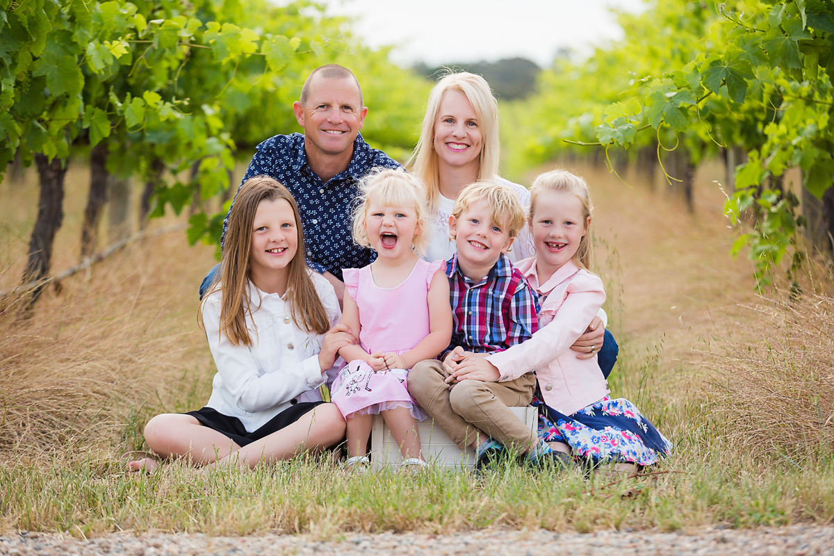 mum and dad and their four children laughing and smiling on a rug in the vineyards at their family photo session by deb elton photography